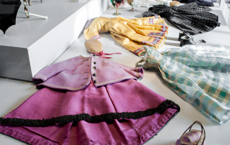 dollhouse: clothes for antique dolls of different types and colors Stock Photo