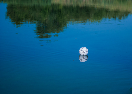 jugadores de futbol: una pelota de f�tbol blanco termina en el agua durante un lanzamiento errado