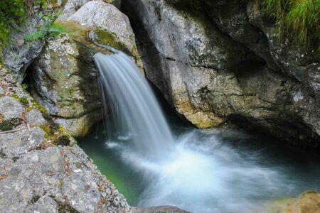 stream of pure water flowing between rocks and trees Standard-Bild