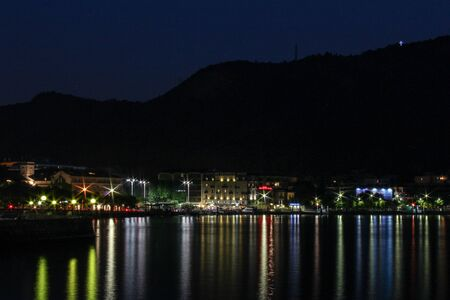 reflected: city lights reflected in the waters of Como Lake Stock Photo
