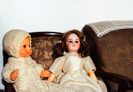 disturbing: Doll blankly and disturbing and sitting on a sofa