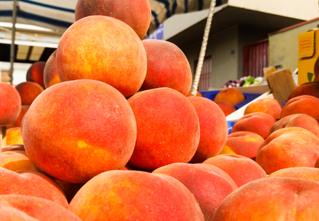 basket of delicious peaches for sale at a street market Standard-Bild