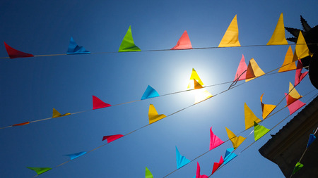 row of colored flags flutter in the sky