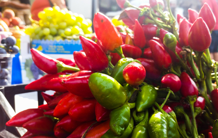 bunch of colorful green and red peppers for sale at a street market