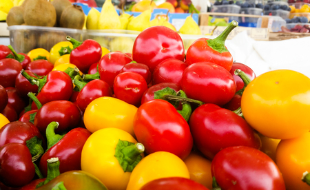 basket of colorful green peppers, red and yellow for sale at a street market
