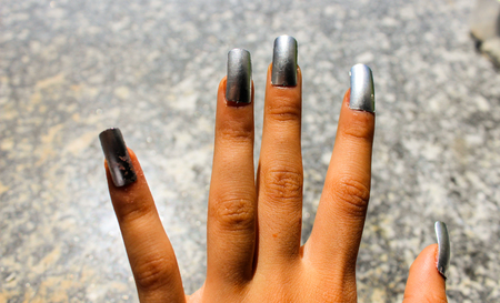 artificial silver-colored nails on a young girls hand