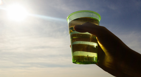 A glass raised in front of the sun god