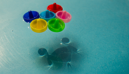 Colored nails float on the water Stock Photo