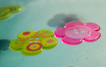 Colorful buttons float on the water