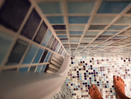 man takes a shower in a nice bathroom with mosaic pearls