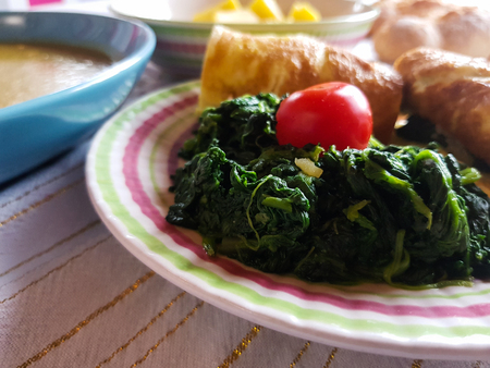 tasty mixed dish with omelette rolls with spinach and red tomato Stock Photo