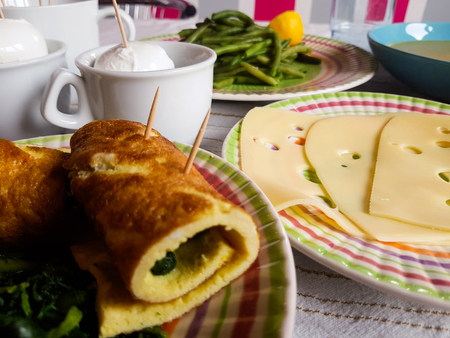 table spread with soup omelette spinach mozzarella rolls and cheese beans