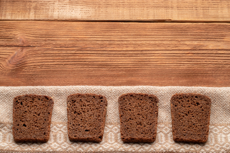 Four slices of rye bread on wooden table. Top view with space for your text.