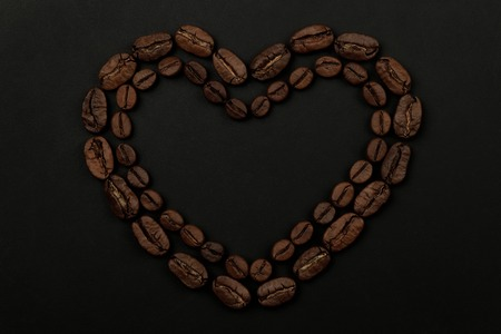Roasted coffee beans placed in a shape of heart on black background Banco de Imagens