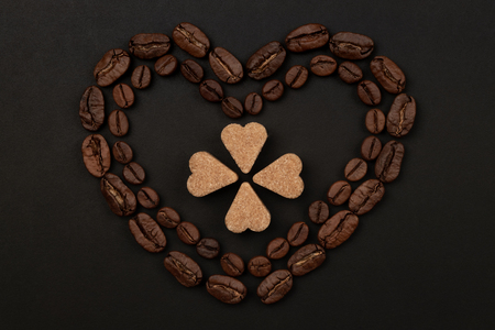 Roasted coffee beans placed in a shape of heart on black background with brown sugar