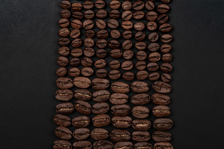 Roasted coffee beans on black background. Top view with space for your text