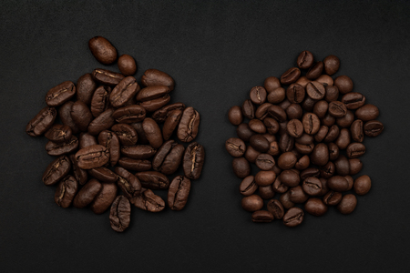 Roasted coffee beans piles flat lay on black background