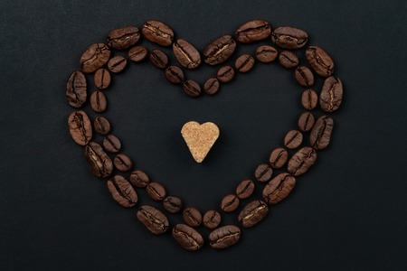 Roasted coffee beans placed in a shape of heart on black background. Flat lay.