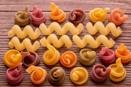 colored pasta on wooden table close up