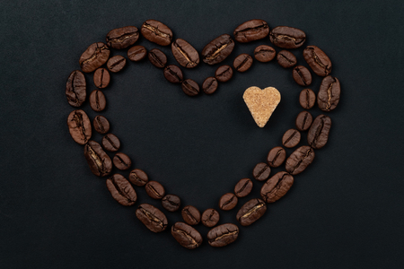 Roasted coffee beans placed in a shape of heart with brown sugar on black background