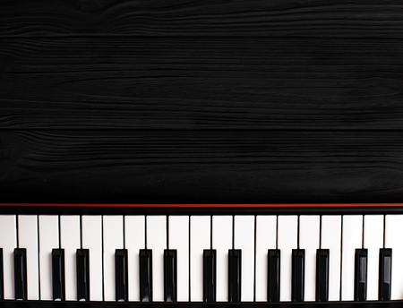 synthesizer keyboard on black wooden background with empty space for text. Reklamní fotografie