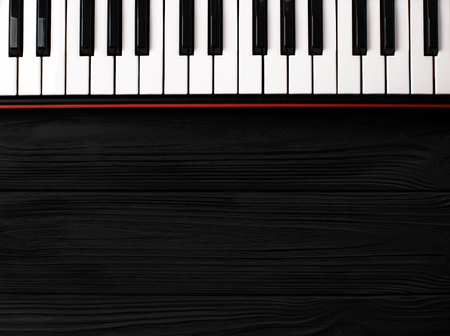 synthesizer keyboard on black wooden background