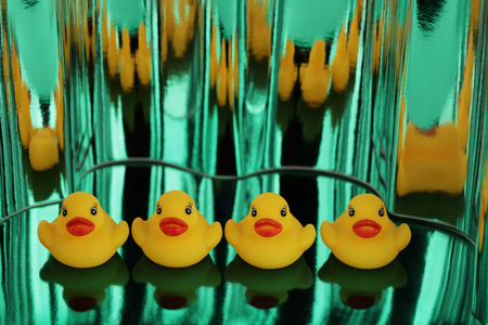 Yellow rubber ducks on green metallic shimmers background. - Image