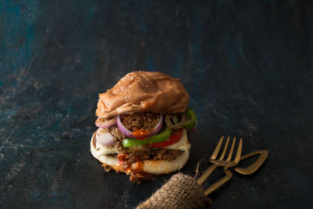 Vegetarian Bean Burger with chili sauce, onions, tomato and bell pepper. Restaurant concept food