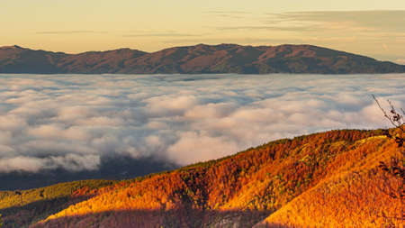 Here we see a beautiful panorama made of clouds that surround the mountain slopes.