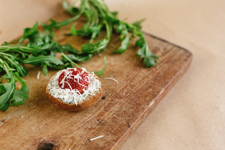parmezan: delicious fresh canape with gorgonzola parmezan and strawberry and arugula on wooden desk on craft background