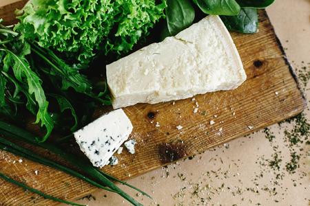 parmezan: delicious fresh salad arugula spinach and parmezan and gorgonzola cheese on wooden cooking board, top view Stock Photo