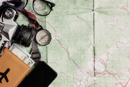 reislust en avontuur concept, oude kompas telefoon fotocamera glazen paspoort en geld liggend op de kaart, bovenaanzicht, ruimte voor tekst, vintage getinte afbeelding Stockfoto