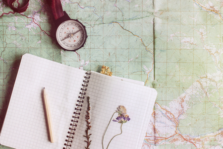 map pencil: wanderlust and adventure concept, compass and notebook with wildflowers and pencil on map, top view, vintage toned image, space for text Stock Photo