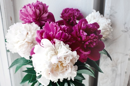 beautiful bunch of peonies in vase on wooden white window sill background, rustic wallpaper concept, space for text