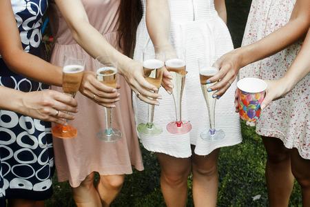 カラフルなメガネを押しながらうれしそうなパーティー夏の公園、ブライダル シャワー、結婚披露宴でシャンパンの乾杯の女性の手