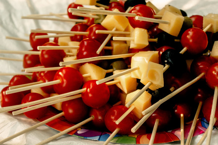 picknick: cherry tomatoes olives cheese on wooden stick appetizer, picnic outdoors, catering buffet at summer celebration