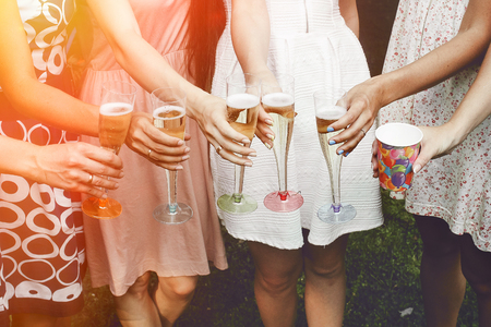 hands of woman holding colorful glasses and toasting champagne at joyful party in summer park, bridal shower or wedding reception