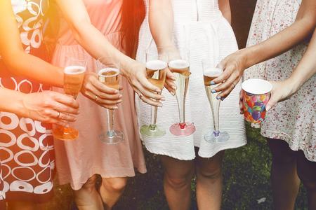 Mani della donna che tiene gli occhiali colorati e tostatura champagne a festa gioiosa nel parco estivo, addio al nubilato o ricevimento di nozze Archivio Fotografico - 64303340