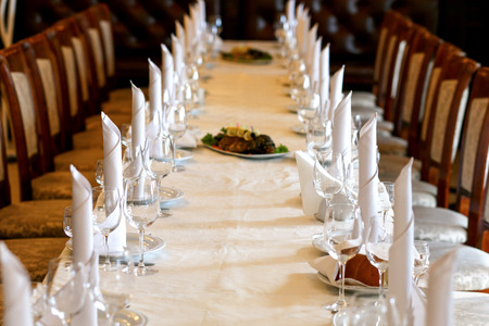 stylish empty glasses and plates at setting for guests at elegant table for wedding reception Stock Photo