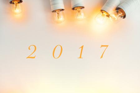 Het teken van 2017 op witte achtergrond met groene takken van spar ongebruikelijke Kerstmis gouden uitstekende slingerlichten, gelukkig nieuw jaar, eenvoudige tekst, hoogste mening Stockfoto - 69912679