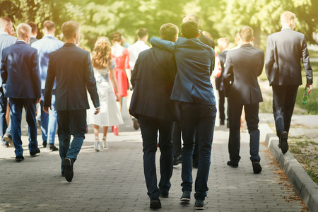 Elegante hombre de confianza en traje de divertirse, grupo de personas caminando, recepción en la boda de lujo, graduación rica en la escuela o la universidad