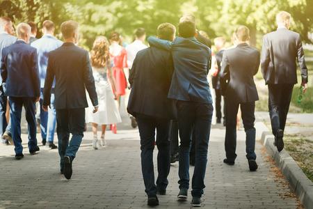 Elegante uomo fiducioso in tuta divertirsi, gruppo di persone a piedi, ricevimento a matrimonio di lusso, laurea ricca a scuola o università