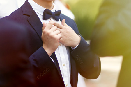 stylish confident man in suit and bowtie, reception at luxury wedding, rich graduation at school or university, business meeting Stock Photo