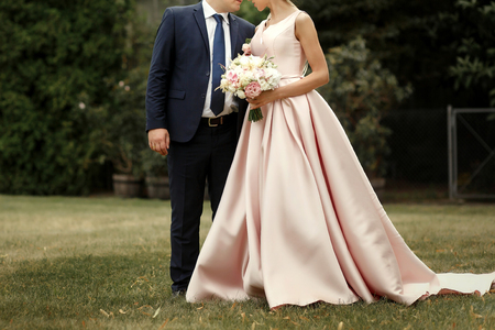 luxury bride and groom posing, stylish wedding couple hugging,  romantic moment at botanical garden, space for text