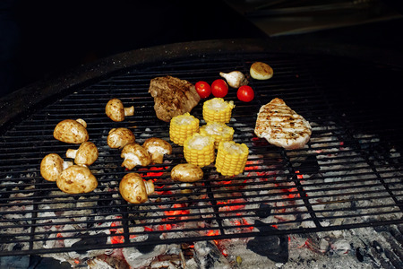 picknick: vegetables and meat grilling. mushrooms corn pepper tomatos garlic on grill. catering in food court at mall concept. space for text. modern kitchen. weekend picknick Stock Photo