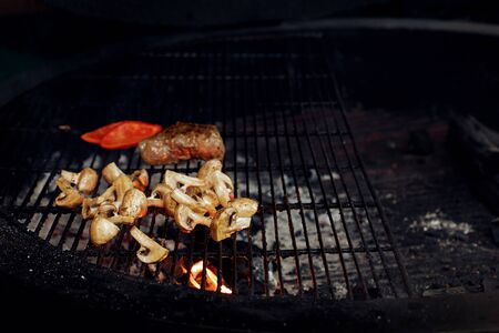picknick: vegetables and meat grilling.  beefsteak mushrooms  tomatos garlic on grill. catering in food court at mall concept. space for text. modern kitchen. weekend picknick