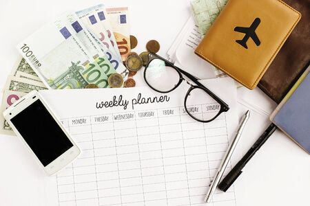 passport money phone with empty screen weekly planner map and glasses on white background,  or insurance papers, travel concept
