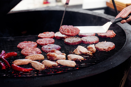 pork meat and chicken cutlets with pepper grilling for burgers. chef working with spatula. catering in food court at mall concept. space for text Stock Photo