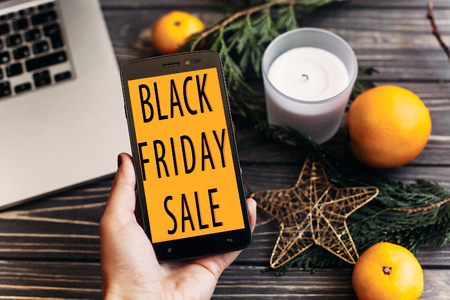 black friday sale. special offer discount text on mobile phone screen in hand message on seasonal rustic background