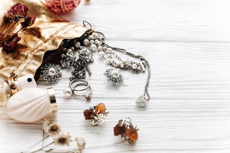 럭셔리 비싼 보석 향수 및 흰색 소박한 나무 테이블에 텍스트를위한 공간. 편평한 누워. 패션 블로거. 현대 여자 액세서리와 풍부한 필수 요소 집합 스톡 콘텐츠